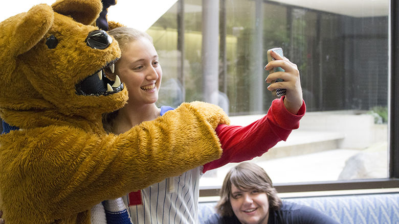 female student taking selfie with Lion Mascot