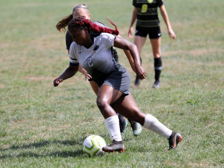 female student kicking ball at soccer match
