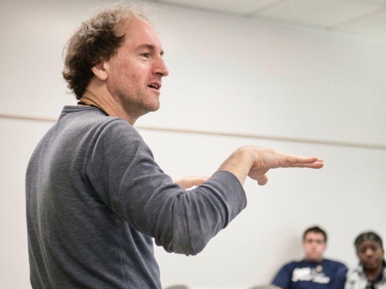 Male professor leaning against desk teaching a class