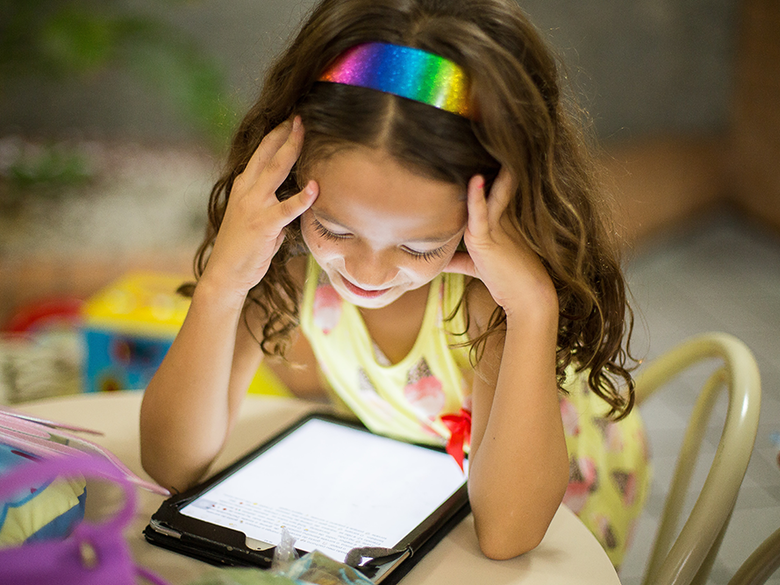 Child reading on tablet.