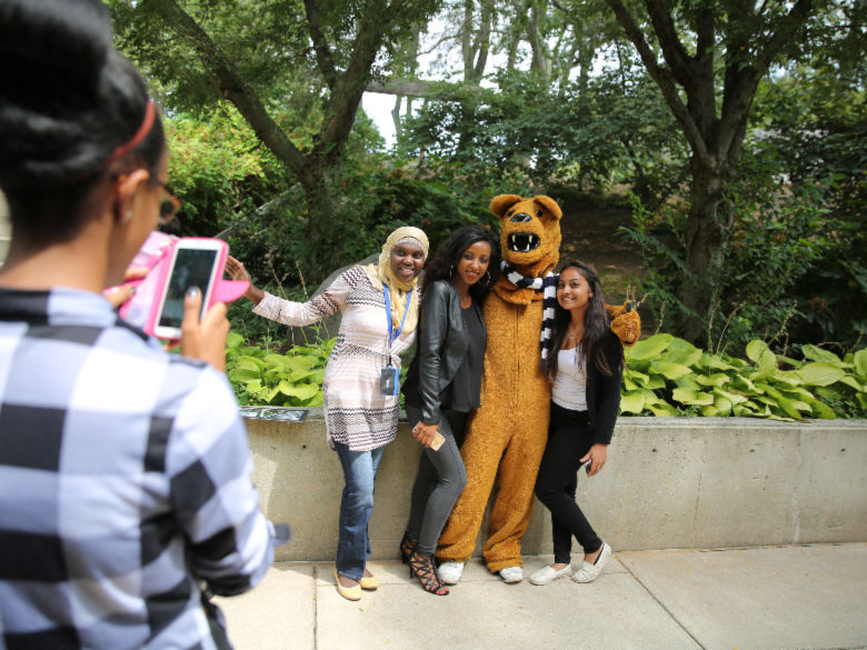 Students taking photo of friends with mascot