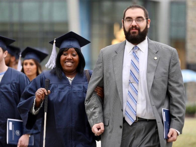 Female student walking to Commencement ceremony with male aid