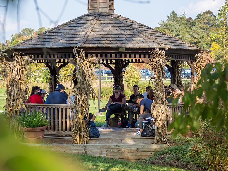 Students sitting in gazebo on campus.