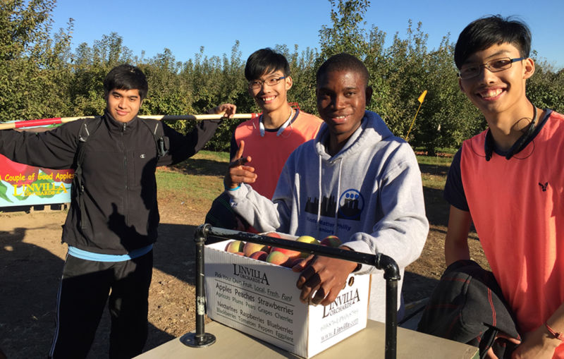 4 male students with box of apples