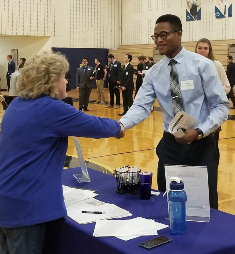 Student shaking hands with a recruiter.