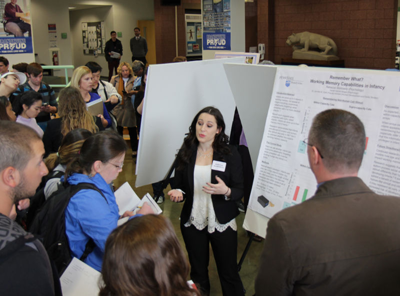 Students discuss their research at a symposium.