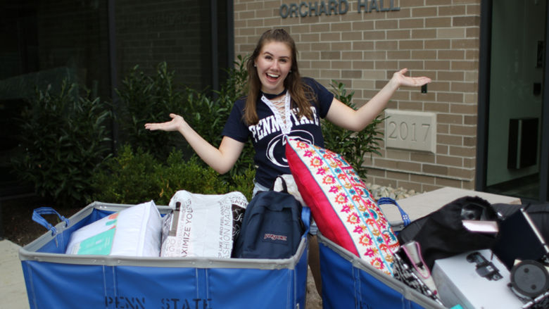 female student standing in front of Orchard Hall with bins to move in