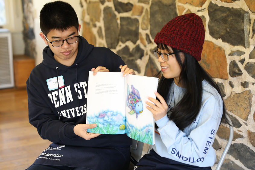 Penn State Brandywine students Eric Tseng and Anna Nguyen read to children at Tyler Arboretum.